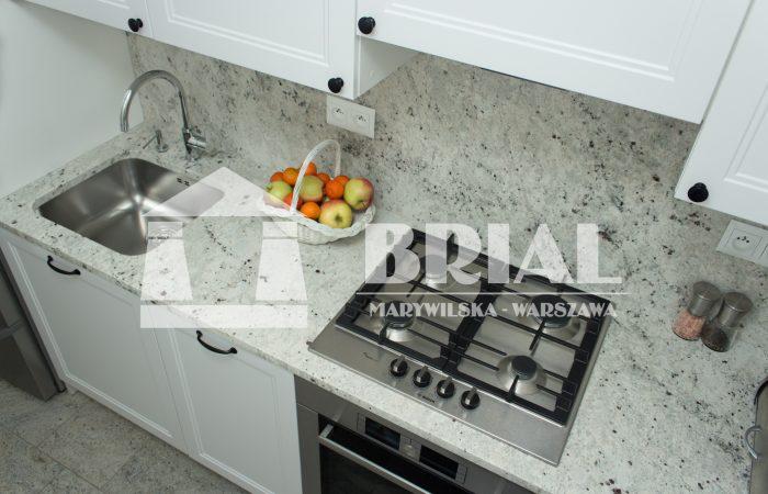 Granit Colonial White - jasny granit na blaty kuchenne, klasyczny granit do kuchni. Blaty kuchenne z granitu Colonial White gr. 3 cm, okładziny ścian z granitu Colonial White gr. 2 cm, otwór obrabiany zlew podblatowy, bateria i dozownik wychodzące z blatu.